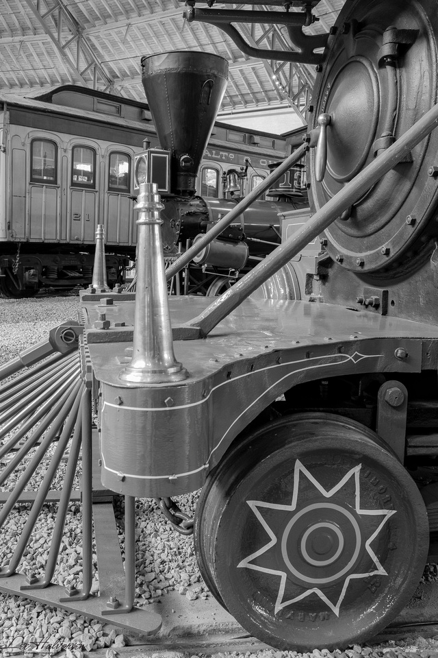 Old, old locomotive with car in background